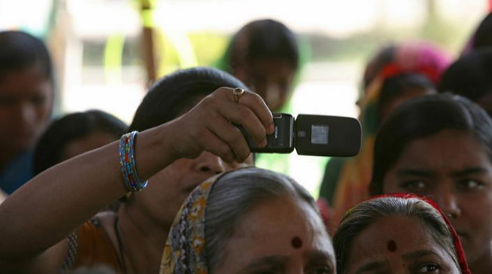 Photo: Woman takes photo with cellphone at a community meeting. Simone D. McCourtie/World Bank via Flickr