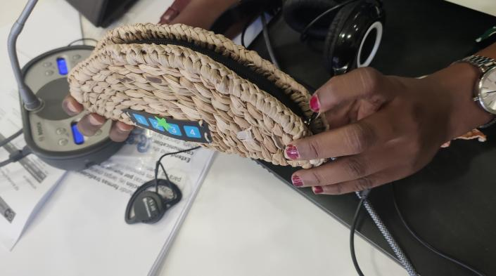 Durante la sesión del 2 de diciembre, una participante muestra el dispositivo Raspberry Zero que usan en su comunidad para grabar y enviar audio a la estación de radio local. Está envuelto en un estuche de junco tradicional para que resulte más familiar a la gente de la comunidad.
