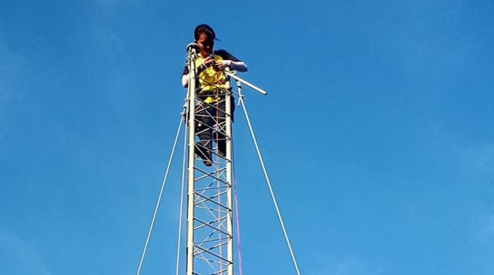 Image description: A person high up on a communications tower. Image source: Village Base Station Project, University of the Philippines